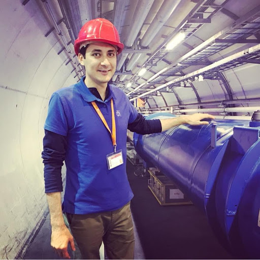 Dr. Adrian Buzatu, PhD graduate from the Department of Physics, is pictured working at CERN in Switzerland. He is wearing a hard hat and a name badge, and is standing next to a piece of CERN equipment.